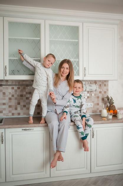 Mère avec enfants dans la cuisine Photo Premium