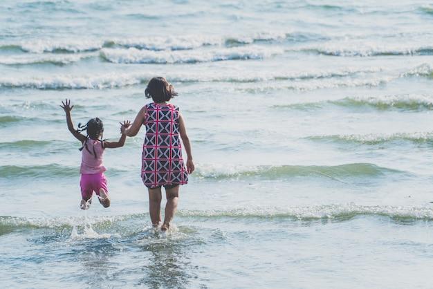Mère et enfants marchant et runnes sur mer au coucher du soleil Photo Premium