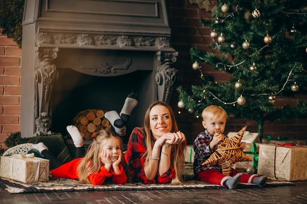 Mère avec enfants par sapin de noël Photo gratuit
