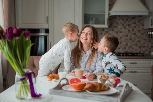 Mère avec enfants prenant son petit déjeuner dans la cuisine Photo Premium
