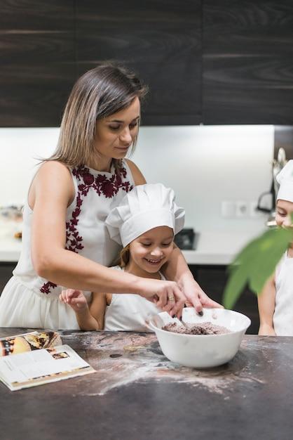 Mère et enfants préparant la pâte sur le comptoir de la cuisine en désordre Photo gratuit