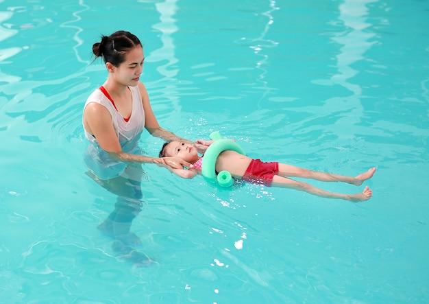 Mère enseignant enfant dans la piscine avec nouille en mousse Photo Premium