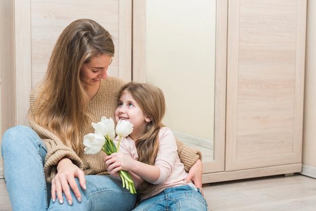 Mère, étreignant, fille, à, fleurs tulipes blanches Photo gratuit