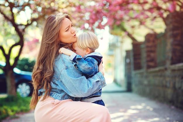 Mère étreignant Son Fils Triste à L'extérieur. Tout-petit Garçon Pleure Dans La Rue. Maternité, Famille Et Style De Vie. Photo Premium