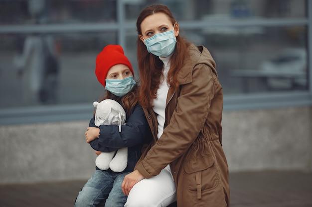 Une Mère Européenne Dans Un Respirateur Avec Sa Fille Se Tient Près D'un Bâtiment.le Parent Enseigne à Son Enfant Comment Porter Un Masque De Protection Pour Se Sauver Du Virus Photo gratuit