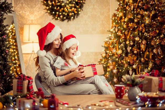 Une mère de famille heureuse et son enfant emballent des cadeaux de noël Photo Premium