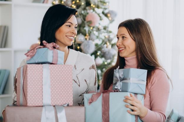 Mère Avec Fille Adulte Avec Des Cadeaux De Noël Par L'arbre De Noël Photo gratuit