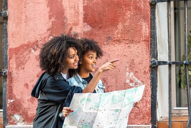 Mère et fille à l'aide d'une carte dans la rue. Photo Premium