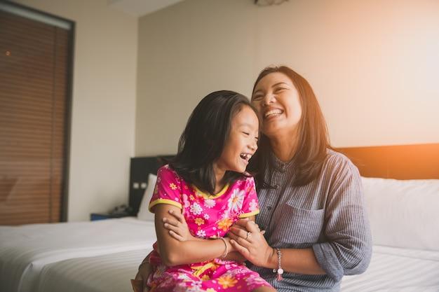 Mère et fille aiment jouer au lit Photo Premium