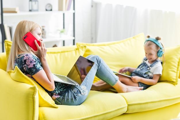 Mère et fille assise sur un canapé en utilisant un appareil électronique Photo gratuit