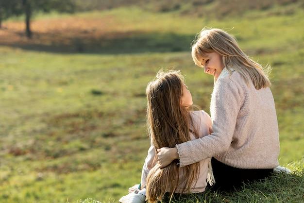 Mère et fille assise dans la nature Photo gratuit