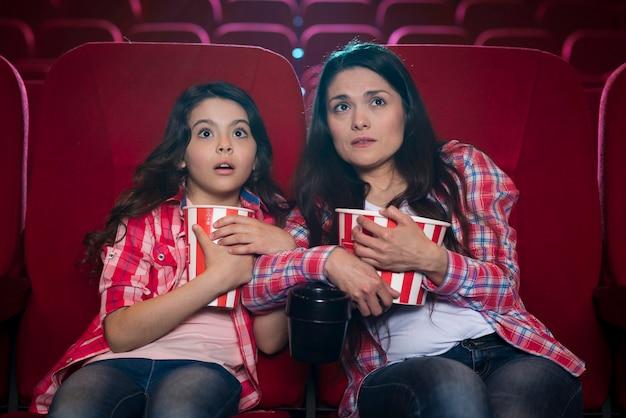 Mère avec fille au cinéma Photo gratuit