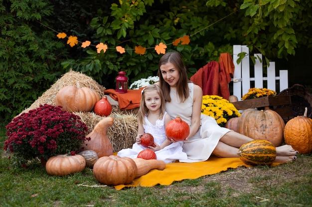 Mère et fille en automne fond avec des citrouilles Photo Premium