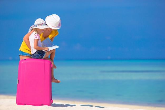 Mère et fille avec bagages et carte sur la plage Photo Premium