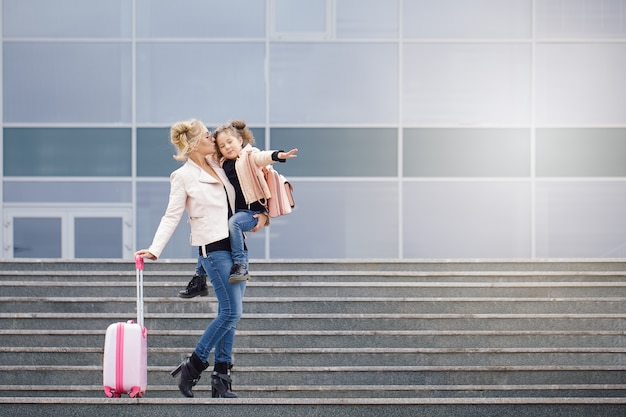 Mère et fille avec des bagages roses en veste rose contre l'aéroport. Photo Premium