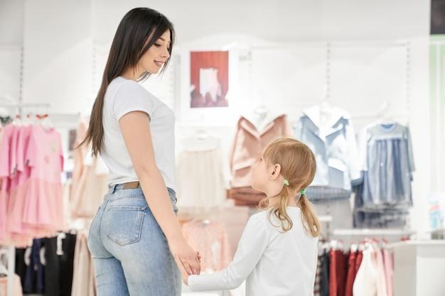 Mère Et Fille Brune En Magasin Avec Des Vêtements Pour Enfants. Photo gratuit
