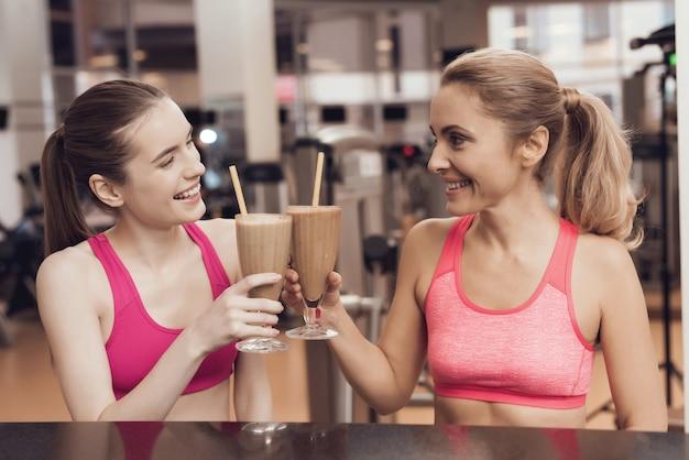 Mère et fille buvant des protéines secoue au gymnase. Photo Premium
