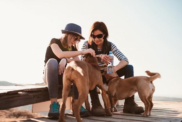 Mère et fille câlinant deux chiens à l'extérieur Photo Premium