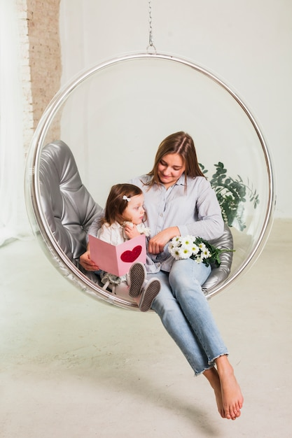 Mère et fille avec carte de voeux en chaise suspendue Photo gratuit