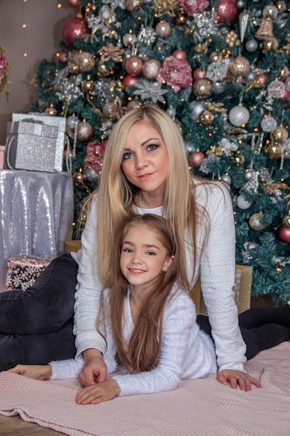 Mère Et Fille à Côté De L'arbre De Noël. Vacances Nouvel An Et Noël. Belle Maman Et Sa Fille. Photo Premium