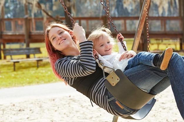 Mère et fille dans une balançoire au parc Photo Premium
