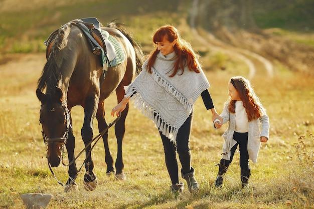 Mère et fille dans un champ jouant avec un cheval Photo gratuit