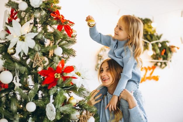 Mère avec fille décorer un arbre de noël Photo gratuit
