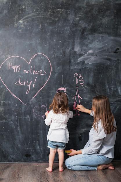 Mère et fille dessinant près de l'inscription heureuse fête des mères Photo gratuit