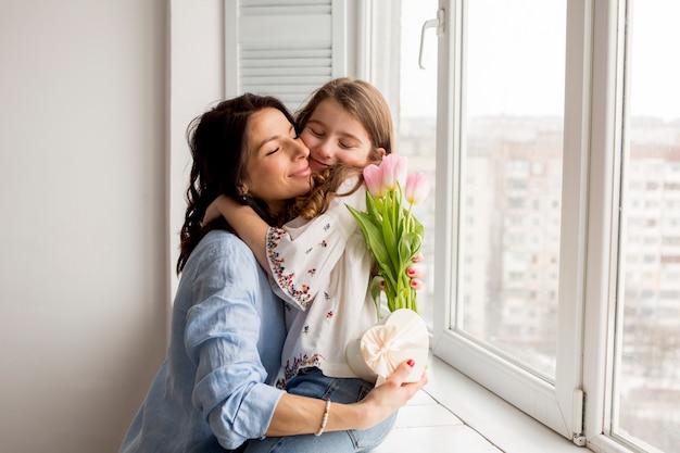 Mère avec fille embrassant des fleurs Photo gratuit