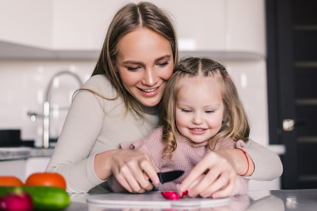 Mère Et Fille Enfant Préparent La Salade De Légumes Photo gratuit