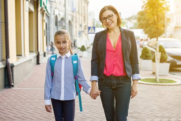 Mère et fille étudiant à pied à l'école. Photo Premium
