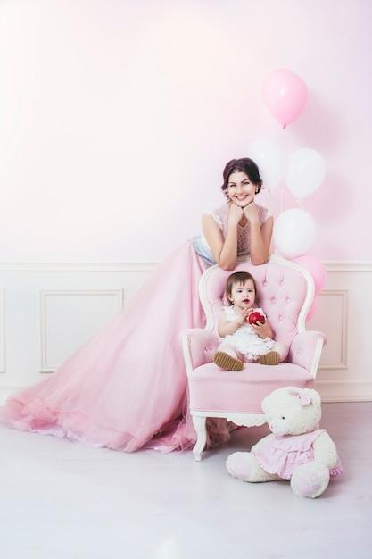 Mère Et Fille à L'intérieur Rose Avec Chaise Vintage Et Ballons Dans De Belles Robes Photo Premium