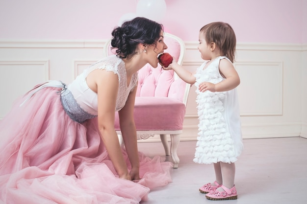 Mère Et Fille à L'intérieur Rose Mangeant Une Pomme Photo Premium