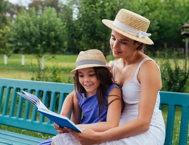 Mère et fille lisant ensemble sur un banc Photo gratuit