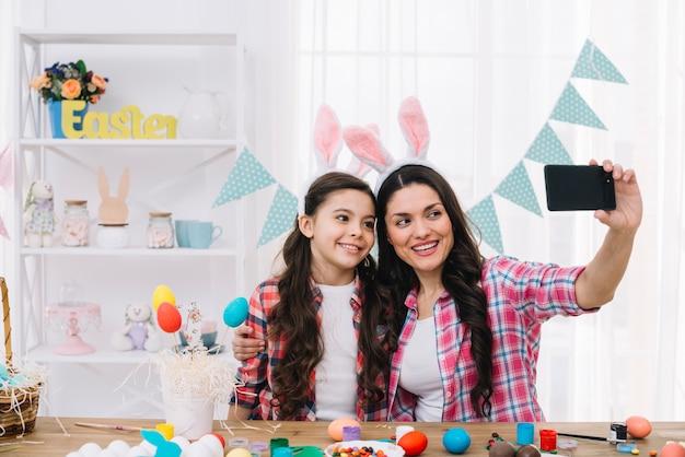 Mère et fille avec oreilles de lapin prenant selfie sur téléphone portable à la maison Photo gratuit