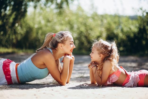 Mère et fille à la plage pratiquant le yoga Photo gratuit