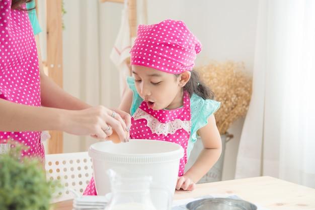 Mère Et Fille Portant Un Tablier Rose Faisant Des Gâteaux Dans La Cuisine. Photo Premium