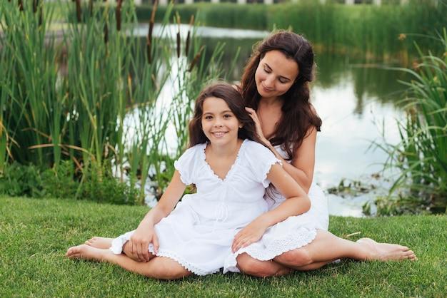 Mère et fille pose dehors Photo gratuit