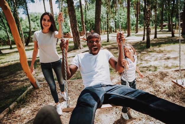 Mère, fille, pousser, papa, balancer, balançoire Photo Premium