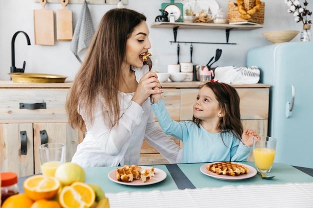 Mère Et Fille Prenant Son Petit Déjeuner Photo gratuit