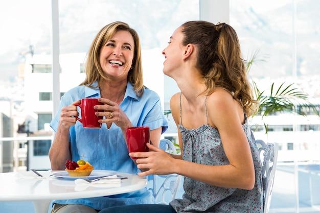 Mère et fille prennent leur petit déjeuner à la maison dans la cuisine Photo Premium