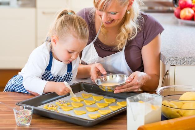 Mère et fille préparant des biscuits ensemble Photo Premium