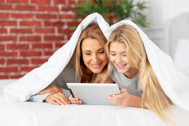 Mère Et Fille à La Recherche Sur Une Tablette Photo gratuit