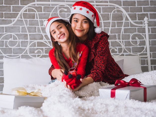 Mère et fille s'embrassent joyeusement et fêtent noël sur le lit Photo Premium