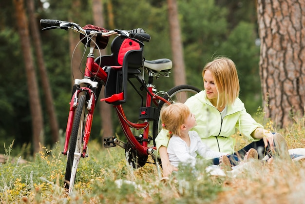 Mère et fille se détendre à côté du vélo Photo gratuit