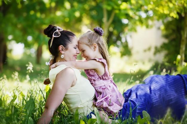 Mère et fille se regardent, sourient, s'embrassent, s'assoient sur l'herbe pendant la journée d'été ensoleillée. Photo Premium