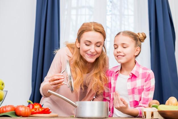 Mère et fille sentant la nourriture préparée dans la cuisine Photo gratuit