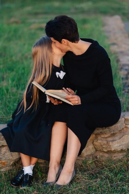 Mère Et Fille Sont Assises Sur Un Banc De Pierre Et Lisent Un Livre. Femme Avec Un Enfant En Robes Noires. Photo Premium