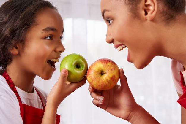 Mère et fille en tabliers mangent des pommes dans la cuisine. Photo Premium
