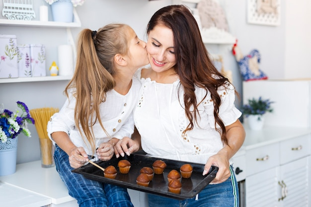 Mère et fille tenant un plateau avec des muffins Photo gratuit